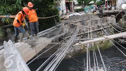 Petugas Suku Dinas Bina Marga Jakarta Barat memperbaiki Jembatan Kali Inspeksi Grogol, Jakarta, (30/5/2016). Pergeseran tanah di bawah Kali Irigasi Grogol sehingga pondasi jembatan bergeser dan permukaan jalan ambles. (Liputan6.com/Helmi Afandi)