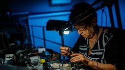 Spesialis reparasi kamera analog, Vessela Draganova sedang bekerja di bengkel kecilnya di Sofia, Bulgaria, Selasa (24/4). Vessela Draganova adalah salah satu spesialis terakhir yang memperbaiki kamera analog di Bulgaria. (AFP PHOTO/Dimitar DILKOFF)