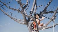 Maudy Ayunda berpose di atas  pohon (dok.Instagram@maudyayunda/https://www.instagram.com/p/BzW4Le1g-ns//Devita