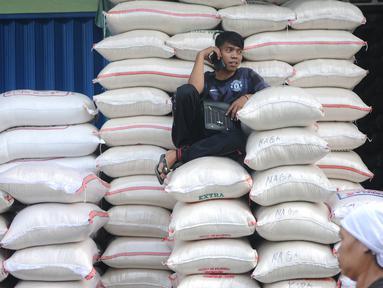 Pekerja duduk ditumpukan beras di pasar induk cipinang, Jakarta, Kamis (13/12). Direktur Pasar Induk Beras Cipinang Arief Prasetyo Adi memastikan, ketersediaan beras di pasar masih aman jelang Natal dan Tahun Baru. (Liputan6.com/Angga Yuniar)