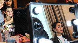 Model saat di make up sebelum pagelaran busana tahunan karya desainer Fetty Rusli di Hotel Mulia Senayan Jumat (26/02). Sebanyak 50 gaun koleksi diperagakan bertepatan dengan ulang tahun Fetty Rusli. (Liputan6.com/Fery Pradolo)