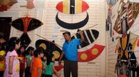 Bersama salah satu pemandu, sejumlah anak berkeliling dan melihat-lihat koleksi layang-layang yang ada di Museum Layang-Layang, Jakarta, (27/9/2014). (Liputan6.com/Helmi Fithriansyah)