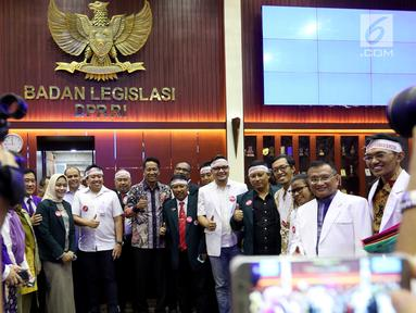 Anggota IDI mengenakan ikat kepala berfoto bersama Ketua Baleg DPR Supratman Andi Agtas  mengikuti Rapat Dengar Pendapat Umum (RDPU) dengan Badan Legislasi DPR di Kompleks Parlemen, Jakarta, Senin (2/4). (Liputan6.com/JohanTallo)