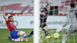 Gelandang Real Madrid, Luka Modric (tengah) melepaskan tendangan yang berbuah gol pertama timnya ke gawang Granada dalam laga lanjutan Liga Spanyol 2020/2021 pekan ke-36 di Los Carmenes Stadium, Granada, Kamis (13/5/2021). Real Madrid menang 4-1 atas Granada. (AP/Fermin Rodriguez)