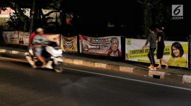 Spanduk-spanduk calon legislatif (caleg) terpampang di sepanjang Jalan Bintaro Permai, Jakarta, Kamis (3/1/2019). Penempatan spanduk di pagar-pagar trotoar dan dinding bengunan membuatnya terlihat semrawut. (Liputan6.com/JohanTallo)