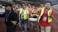 Seorang suporter Malaysia dievakuasi petugas karena terjatuh ketika dievakuasi karena serangan suporter Timnas Indonesia saat laga Kualifikasi Piala Dunia 2022 di SUGBK, Jakarta, Kamis (5/9). (Bola.com/Vitalis Yogi Trisna)