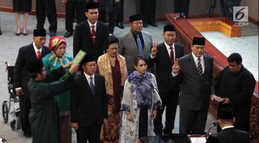 Sembilan anggota DPR membacakan sumpah dan janji saat Pergantian Antar Waktu (PAW) pada Rapat Paripurna DPR, Jakarta, Selasa (2/10). Sembilan anggota PAW tersebut terdiri dari empat fraksi. (Liputan6.com/JohanTallo)