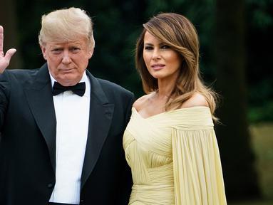 Presiden AS Donald Trump didampingi Ibu Negara, Melania Trump melambaikan tangan sesaat akan meninggalkan Winfield House di London, Kamis (12/7). Melania Trump dan Donald Trump tengah berada di Inggris untuk kunjungan kenegaraan.. (AFP/Brendan Smialowski)