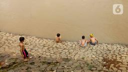Sejumlah anak bermain di Bantaran sungai Kanal Banjir Barat, Tanah Abang, Jakarta, Sabtu (4/1/2020). Minimnya lahan bermain terpaksa membuat anak-anak harus bermain di bantaran Banjir Kanal Barat meskipun dapat membahayakan keselamatan dirinya. (Liputan6.com/Angga Yuniar)