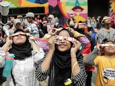 Pengunjung mengamati gerhana matahari cincin memakai kacamata khusus di Planetarium Taman Ismail Marzuki, Jakarta, Kamis (26/12/2019). Planetarium menyediakan sekitar 10 teleskop dan kacamata khusus agar pengunjung bisa menyaksikan gerhana matahari cincin dengan aman. (Liputan6.com/Faizal Fanani)