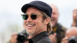 Aktor Brad Pitt tersenyum saat tiba menghadiri pemutaran film 'Once Upon a Time in Hollywood' selama Festival Film Cannes Internasional ke-72 di Prancis (22/5/2019).  Brad Pitt tampil santai mengenakan jeans hitam, kemeja polo hitam, kaca mata dan topi. (AP Photo/Joel C Ryan)