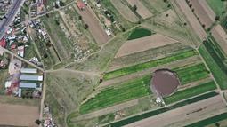 Pemandangan udara dari sinkhole yang ditemukan oleh petani di lahan pertanian di Santa Maria Zacatepec, negara bagian Puebla, Meksiko, Senin (1/6/2021). Sinkhole itu dengan cepat membesar menjadi 60 meter pada hari Senin. (JOSE CASTAÑARES/AFP)