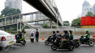 Sejumlah warga nekat menyeberang di bawah JPO sisi barat Polda Metro Jaya di Jalan Jenderal Sudirman, Jakarta, yang ditutup dan dibongkar, Senin (23/11). Pembongkaran dilakukan karena adanya perbaikan saluran air. (Liputan6.com/Yoppy Renato)