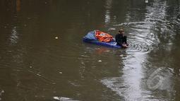 Masih banyak warga bantaran kali Ciliwung Jakarta yang memanfaatkan air kali untuk kehidupan sehari - hari. Tampak seorang pemulung mengumpulkan sampah plastik yang ada di kali Ciliwung Jakarta, Jumat (20/2/2015). (Liputan6.com/JohanTallo)