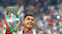 Cristiano Ronaldo membawa tropi Piala Eropa 2016 usai memenangkan laga melawan Prancis di Stade de France, Senin (11/7). Ronaldo menjadi Pencetak Gol Terbanyak sepanjang perhelatan Piala Eropa berlangsung sebanyak 9 gol. (REUTERS)
