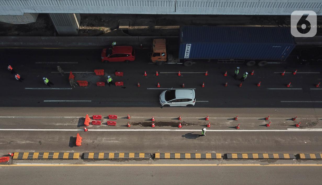 Foto udara suasana  pos penyekatan pemudik Tol Cikarang Barat, Kabupaten Bekasi, Jawa Barat, Minggu (9/5/2021). Petugas gabungan memperketat pemeriksaan dokumen kendaraan yang melintasi pos penyekatan pemudik jelang H-3 perayaan Hari Raya Idul Fitri 1442 H. (Liputan6.com/Herman Zakharia)