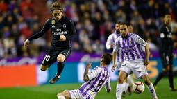 Gelandang Real Madrid, Luka Modric berusaha melewati pemain Real Valladolid, Luismi Sanchez selama pertandingan lanjutan La Liga Spanyol di stadion Jose Zorrilla,Valladolid (10/3). Madrid menang telak 4-1 atas Valladolid. (AP Photo/Alvaro Barrientos)