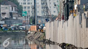 Pekerja menyelesaikan pekerjaanya saat pemasangan sheet pile di Kali Sunter, Kemayoran, Jakarta, Selasa (26/7). Pemasangan turap tersebut untuk mencegah terjadinya banjir di musim penghujan.(Liputan6.com/Yoppy Renato)