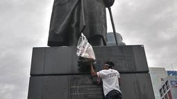 Seorang aktivis menaruh bunga  di depan patung Jenderal Soedirman, Jakarta, Rabu (14/11). Aksi tabur bunga dan hening cipta ini dalam rangka memperingati Hari Pahlawan dan menghormati jasa-jasa Jenderal Soedirman. (Merdeka.com/ Iqbal S. Nugroho)