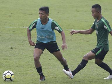 Pemain Timnas Indonesia U-23, T. M. Ichsan, berebut bola dengan Sani Rizki, saat latihan di Stadion Madya, Jakarta, Rabu (13/3). Latihan ini merupakan persiapan jelang Kualifikasi Piala AFC U-23. (Bola.com/Vitalis Yogi Trisna)