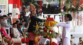 Presiden Joko Widodo (tengah) menyerahkan duplikat bendera pusaka kepada Paskibraka Tarrisa Maharani Dewi saat Upacara Peringatan Detik-detik Proklamasi Kemerdekaan ke-73 di Istana Merdeka, Jakarta, Jumat (17/8). (Liputan6.com/HO/Bian)