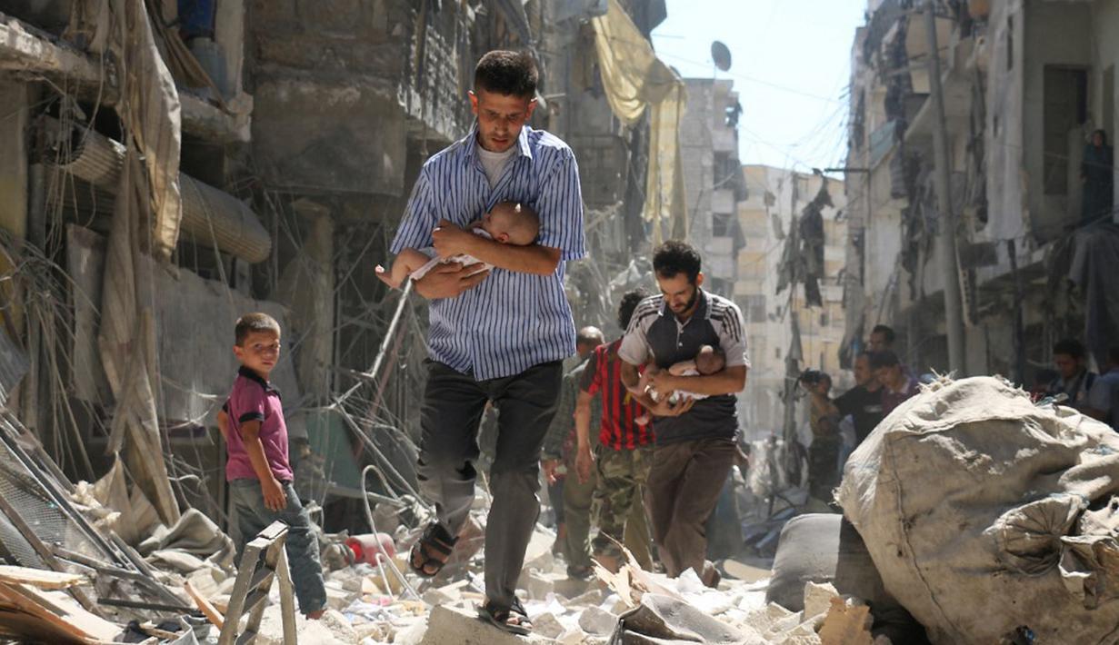 Para pria menggendong bayi saat berjalan melewati puing-puing bangunan yang hancur usai serangan udara di daerah yang dikuasai pemberontak di Salihin, Aleppo, Suriah, 11 September 2016. (Photo by Ameer al-HALBI/AFP)