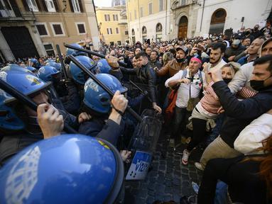 Polisi anti huru-hara (kiri) menggunakan tongkat untuk melawan pengunjuk rasa saat bentrokan dalam aksi protes oleh pemilik restoran dan aktivitas bisnis lainnya di luar parlemen di Piazza Montecitorio di Roma, Selasa (6/4/202). Mereka menuntut untuk membuka kembali bisnis. (Filippo MONTEFORTE/AFP)