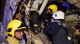 Petugas berusaha mengevakuasi korban kecelakaan yang melibatkan truk dan bus di jalan raya antara Ibri dan Fahud, Oman bagian barat, Selasa (1/3). Sebanyak 18 orang dari beberapa kewarganegaraan tewas dan 14 lainnya luka-luka. (STRINGER/Omani Police/AFP)