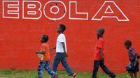 Sejumlah anak berjalan melewati dinding yang bertuliskan 'Ebola' di Monrovia, Liberia, 31 Agustus 2014. Liberia melarang para awak kapal untuk berlabuh di negara-negara yang rentan epidemi Ebola. (AFP PHOTO/DOMINIQUE FAGET)