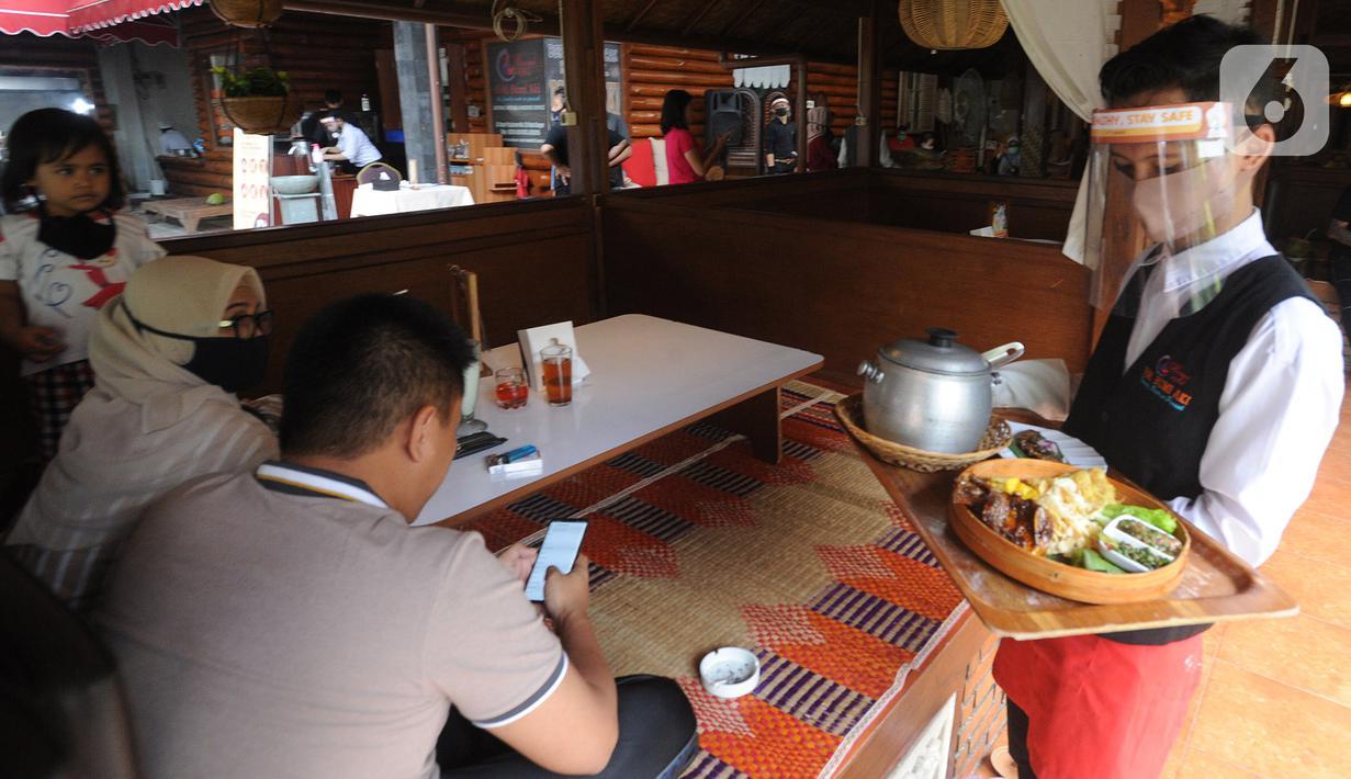 Pramusaji menggunakan pelindung wajah, masker dan sarung tangan di Rumah Makan Bumi Aki, Pajajaran, Kota Bogor, Minggu  (31/5/2020). Sejumlah restoran dan rumah makan di Bogor mulai membuka layanan makan di tempat dengan protokol kesehatan ketat guna mengatasi COVID-19. (merdeka.com/Arie Basuki)