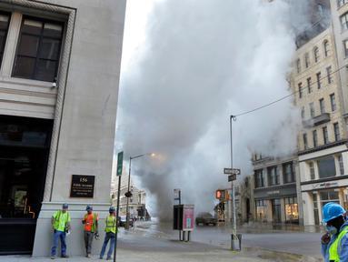Sebuah pipa uap meledak menyebabkan gumpalan besar asap putih mengepul ke udara di Distrik Flatiron, Manhattan, Kamis (19/7). Pipa uap  yang dipasang di bawah Fifth Avenue dan 21st Street tersebut meledak pada pagi waktu setempat. (AP Photo/Richard Drew)