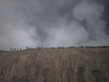 Wisatawan dan anggota suku Tengger mendaki Gunung Bromo saat Festival Yadnya Kasada di Probolinggo, Jawa Timur (10/7). Warga Tengger melakukan ritual lempar hasil bumi sebagai wujud syukur pada Sang Hyang Widi. (AFP Photo/Juni Kriswanto)