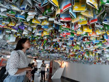 """Seorang wanita melihat instalasi seni gantung sekelompok seniman yang terbuat dari sisa-sisa plastik, kaleng dan wadah di sebuah pameran """"Reduce the Litter"""" di Pusat Kebudayaan Prancis di Hanoi (15/7/2019). Pameran ini mengambil perspektif tentang produksi dan konsumsi. (AFP Photo/Nhac Nguyen)"""