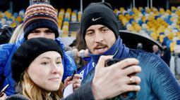 Penggemar wanita berselfie dengan gelandang Chelsea, Eden Hazard selama sesi pelatihan di NSC Olympiyskiy, Kiev, Ukraina (13/3). Pada leg pertama Chelsea menang telak atas Dynamo Kiev 3-0 di Stamford Bridge. (Reuters/Valentyn Ogirenko)
