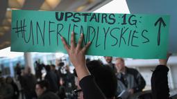 Demonstran mengecam tindakan polisi yang mengeluarkan penumpang tidak manusiawi di pesawat United Airlines di Bandara Internasional O'Hare, Chicago, AS, Selasa (11/4). (Scott Olson / Getty Images / AFP)