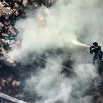 Seorang pengunjuk rasa menggunakan alat pemadam kebakaran saat bentrok dengan polisi anti huru hara dalam menentang kudeta militer di Yangon (28/2/2021). Sedikitnya 18 orang tewas setelah Polisi Myanmar menembaki pengunjuk rasa di seluruh negeri pada hari Minggu. (AFP/Sai Aung Main)