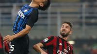 Pemain Inter Milan, Yuto Nagatomo menyundul bola di depan pemain AC Milan, Fabio Borini pada pekan kedelapan Liga Italia di Stadion Giuseppe Meazza, Minggu (15/10). Gol Inter Milan diborong oleh Mauro Icardi, 3-2. (AP/Antonio Calanni)