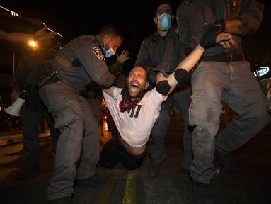 Polisi menahan seorang pengunjuk rasa selama demonstrasi menentang tindakan lockdown di Tel Aviv, Israel, Kamis (1/10/2020). Pengunjuk rasa meyakini lockdown ditujukan untuk mengekang protes terhadap Perdana Menteri Israel Benjamin Netanyahu. (AP Photo/Sebastian Scheiner)