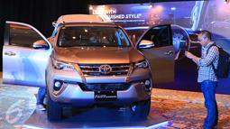 Pengunjung saat melihat mobil All New Fortuner di JCC, Jakarta, Jumat (22/1). Toyota Astra Motor (TAM) agen pemegang merek mobil Toyota di Indonesia resmi meluncurkan All New Fortuner. (Liputan6.com/Angga Yuniar)