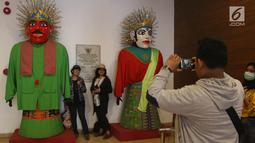 Pengunjung berpose di samping ondel-ondel yang ada di Museum Fatahillah dan Museum Wayang, Kota Tua, Jakarta, Selasa (26/6). Pemprov DKI menggratiskan biaya masuk sejumlah museum pada hari ini. (Liputan6.com/Arya Manggala)