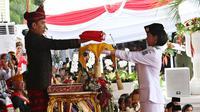 Presiden Jokowi menyerahkan Bendera Merah Putih kepada Fariza Putri Salsabila, anggota Pasukan Pengibar Bendera Pusaka (Paskibraka), saat Upacara Peringatan Detik-detik Proklamasi 17 Agustus di Istana, Jakarta, Kamis (17/8). (Liputan6.com/Pool)