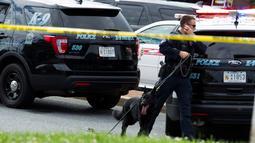 Polisi satwa atau K9 menelusuri lokasi kejadian setelah penembakan brutal di kantor surat kabar lokal di Annapolis, AS, Kamis (28/6). Polisi belum diketahui motif di balik aksi penembakan yang dilakukan di koran Capital Gazette itu. (AP/Jose Luis Magana)
