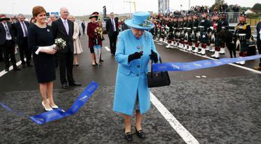 Ratu Inggris Elizabeth II memotong pita dalam peresmian jembatan Queensferry di Skotlandia, Minggu (4/9). Jembatan Queensferry resmi dibuka untuk menghubungkan antar ibu kota Edinburgh dengan bagian utara Skotlandia. (Andrew Milligan/PA via AP)