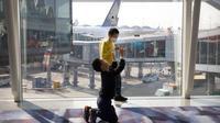 Seorang anak yang mengenakan masker bermain dengan anak laki-laki lain di Bandara Internasional Hong Kong di Hong Kong, Selasa (21/1/2020). Masker terjual habis dan pemeriksaan suhu di bandara dan stasiun kereta api menjadi norma baru di China menyusul merebaknya wabah virus corona. (AP/Ng Han Guan)