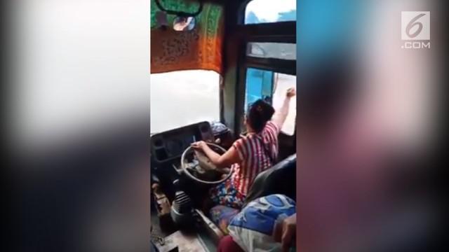 Emak-emak gaul bekerja sebagai sopir sekaligus kernet bus. Gayanya nyentrik dan unik hingga jadi perhatian.