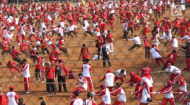 Aparatur Sipil Negara (ASN) Kementerian Dalam Negeri menarik lawan dalam lomba tarik tambang di Lapangan Banteng, Jakarta, Jumat (2/8/2019). Kemendagri bersama Badan Pengelola Nasional Pengelola Perbatasan (BNPP) memecahkan rekor MURI yang diikuti sebanyak  1.200 peserta. (Liputan6.com/Angga Yuniar)