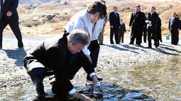 Presiden Korsel Moon Jae-in ditemani istrinya, Kim Jung-sook memasukkan air kawah ke dalam botol di Gunung Paektu, Korut, Kamis (20/9). Gunung ini menjadi propaganda untuk melegitimasi tiga generasi pemerintahan Kims. (Pyongyang Press Corps Pool via AP)