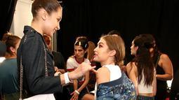Model Bella Hadid berbincang dengan kakaknya, Gigi Hadid mdi belakang panggung fashion show Anna Sui selama New York Fashion Week, AS (14/9). (AFP Photo/Astrid Stawiarz)