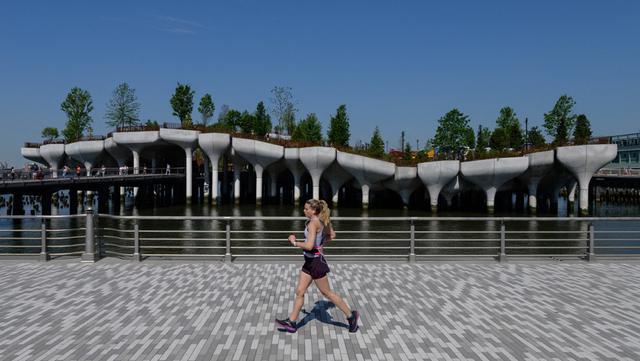 Seorang pelari berlari melewati 'Pulau Kecil', taman umum baru dan gratis di Hudson River Park, New York City, Amerika Serikat, 21 Mei 2021. Taman yang diresmikan pada 21 Mei 2021 tersebut menghabiskan dana sebesar USD USD 260 juta. (Angela Weiss/AFP)
