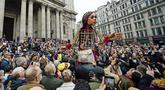 Boneka raksasa Little Amal disambut ratusan warga saat tiba di kota London, Inggris, Sabtu (23/10/2021). Little Amal merupakan boneka berukuran raksasa yang menjadi simbol pengungsi anak dari Suriah.(Aaron Chown/PA via AP)